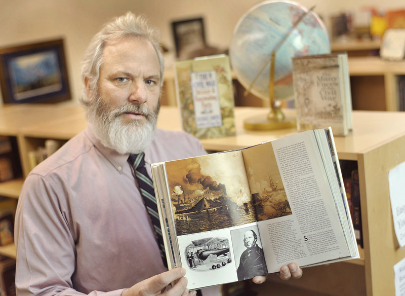 Andrew Bryan of Holden holds a National Geographic book that has a depiction of the famous naval battle at Hampton Roads, Va., between the Merrimack and the Monitor in 1862 during the Civil War. His great-great-great-uncle served aboard the USS Monitor.