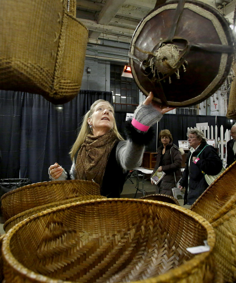 Carmen Serier of Bowdoinham looks at hand-made baskets at the The Children's Initiative booth during the opening night of the Portland Flower Show at the Portland Company Complex in Portland on March 6, 2013. The baskets are made in a village in Vietnam with the proceeds used to build schools.