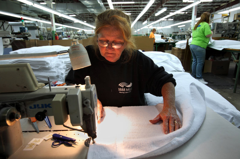 Karen Pias sews the finishing edge on a towel at 1888 Mills in Griffin, Ga. Walmart will sell 1888's Made Here towels, as part of the onshoring trend moving some manufacturing back to the U.S., but technology advancements mean fewer workers are needed for production.