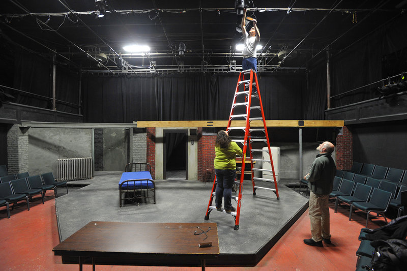 UMF student Richard Russell, an actor in an upcoming play, attaches colored gels to stage lights with assistance from stage crew member Leigh Welch (on ladder) and theater designer Dan Spilecki.