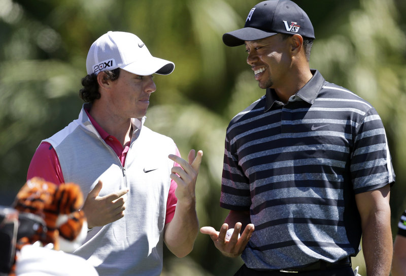 Rory McIlroy, left, shares a moment with Tiger Woods during Thursday's outing in Doral, Fla., but his 73 left him with little to smile about as he's still finding last year's success a tough act to follow.