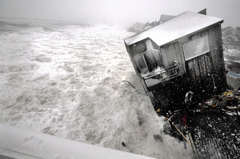 A house on the Plum Island seacoast in Newbury, Mass., sits partially collapsed into the churning surf, driven by winds from a slow-moving ocean storm at high tide Friday. The storm dropped up to a foot of snow on some parts of New England.