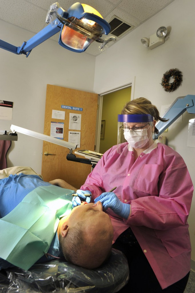 Dental hygienist Torey Richard cleans a patient's teeth at Clinical Services. Closing the clinic will ultimately prove more costly for the state, said Rep. Denise Harlow.