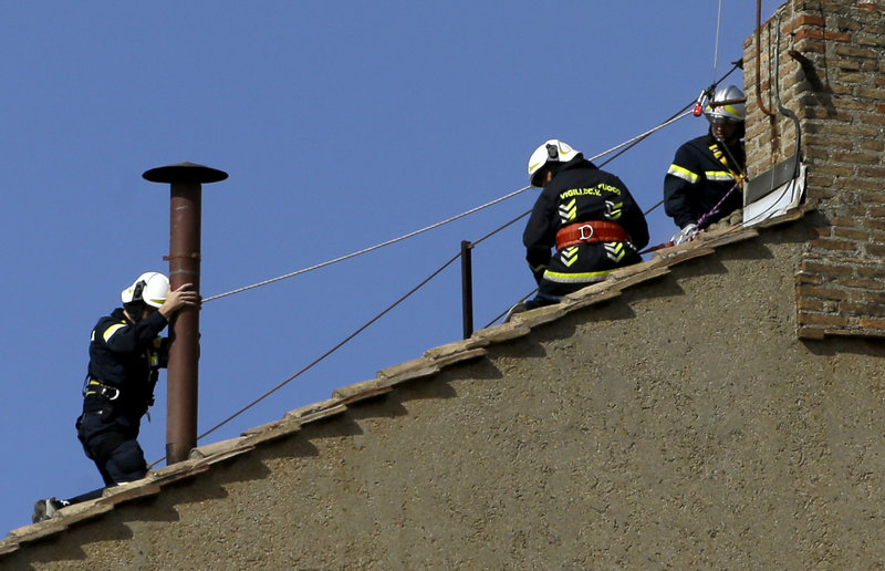 Firefighters place the chimney on the roof of the Sistine Chapel on Saturday at the Vatican, where cardinals will gather to elect the new pope. Smoke from the burning ballot papers will tell the world when a decision has been reached on a successor to Benedict XVI.