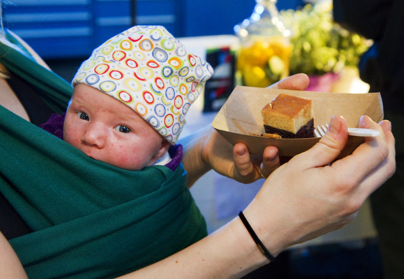 Emily Hickey, with 3-week-old Marya in a sling, takes a bite of a dessert sample Sunday at the Signature Event culminating Restaurant Week.