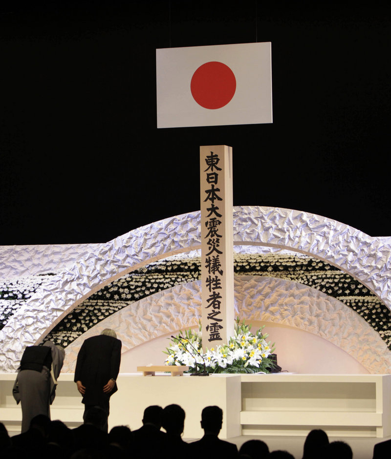 Japanese Emperor Akihito, right, and Empress Michiko bow Monday to pay tribute to the victims of the 2011 earthquake and tsunami at the national memorial service in Tokyo.
