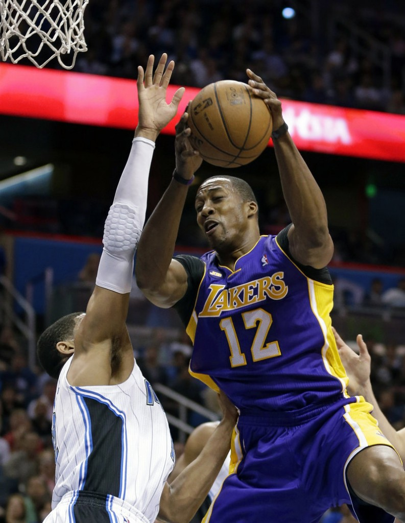Dwight Howard of the Lakers goes up against Orlando's Tobias Harris in Tuesday's 98-81 win at Orlando, Fla. Howard tied his NBA record of 39 free-throw attempts.