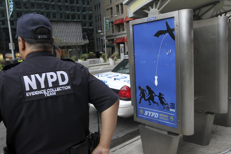 "In this September 2012 file photo, New York City police officers wait to remove a fake NYPD ""public service"" ad at a public phone bank in Lower Manhattan. The ads, installed by Essam ""Adam"" Attia of Maine, depict the police force as a drone-deploying Big Brother."