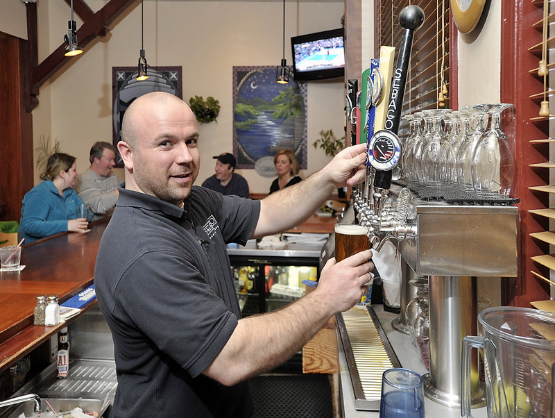 Bartender Chris Salamone pours a Frye's Leap draft from one of the many Sebago Brewing taps at the popular spot in Gorham.