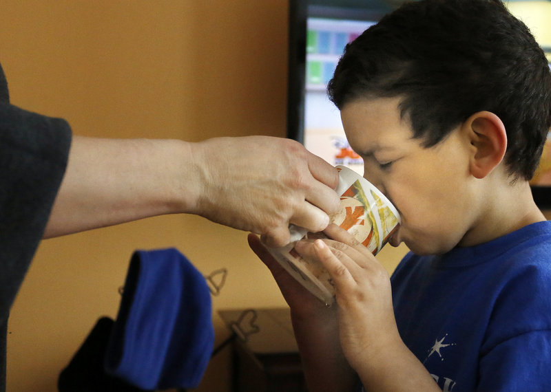Marie Beaulieu, left, helps Shavar drink from a cup of water to take medication in the living room of their Jay home. Some adoptive foster parents in Maine will lose 25 percent of their adoption subsidy as a result of a supplemental state budget passed in February.