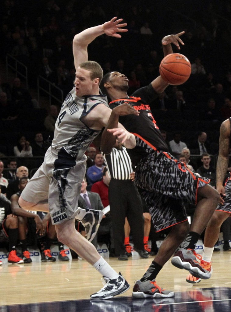 Georgetown's Nate Lubick, left, and Cincinnati's Titus Rubles get locked up as they battle for a rebound during the Hoya's 62-43 win in a Big East quarterfinal game at New York on Thursday.
