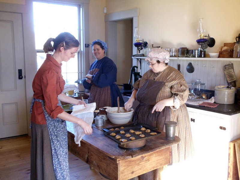 Volunteers Anne Feith, Mary Castonguay and Shelley Cox make cookies in the farmer's cottage at the Washburn-Norlands Living History Center.