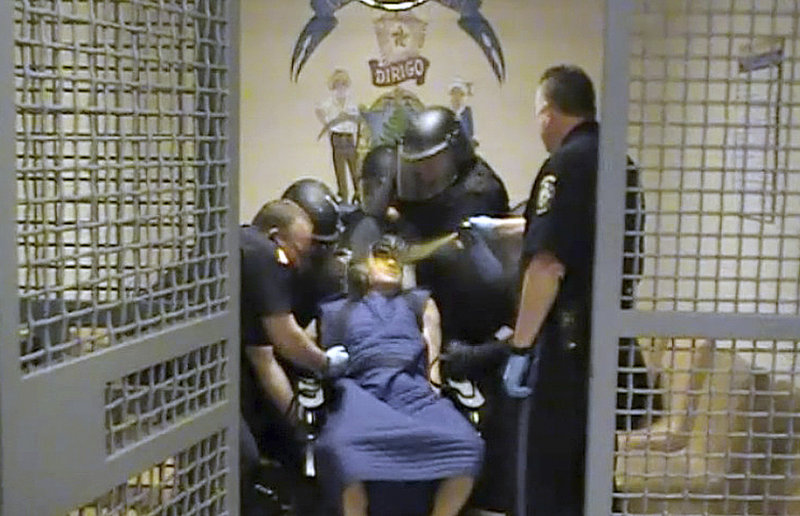 In this video image, Capt. Shawn Welch sprays OC spray into the face of Paul Schlosser who is bound in a restraint chair after the inmate spit at an officer on June 10, 2012.