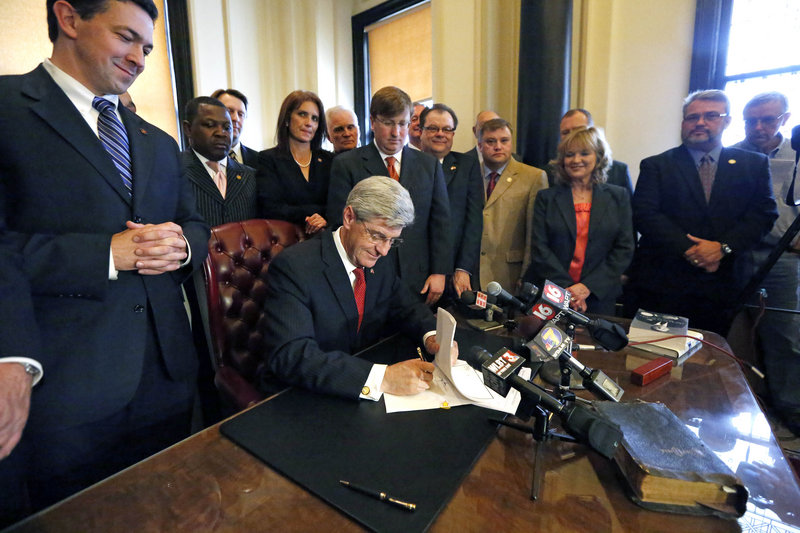 Lawmakers and others watch Gov. Phil Bryant sign the Mississippi Student Religious Liberties Act allowing students to express religious sentiments without fear of reprisals.