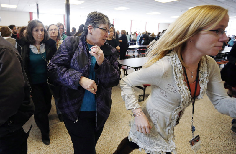 Participants rush out of the cafeteria after hearing gun shots during a lockdown exercise at Milford High School in Milford, Mass., Friday, March 15, 2013. More than 500 teachers, administrators, cafeteria workers and school custodians participated in the training program that taught about alternatives to staying in lockdown during a school shooting, including fighting back. (AP Photo/Michael Dwyer)