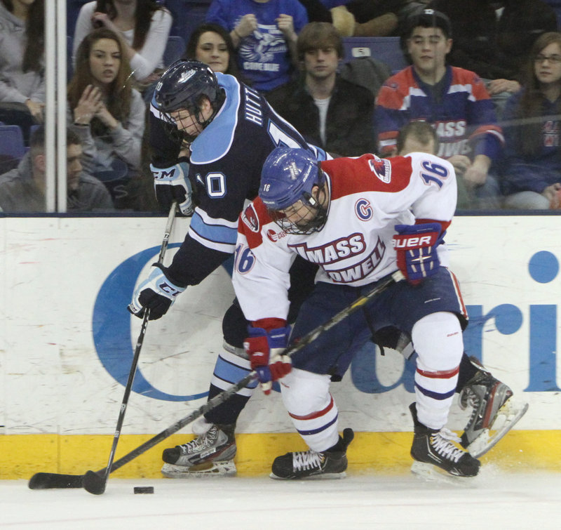 Maine's Ben Hutton, left, and UMass-Lowell's Riley Wetmore vie for the puck during the first period Friday night.