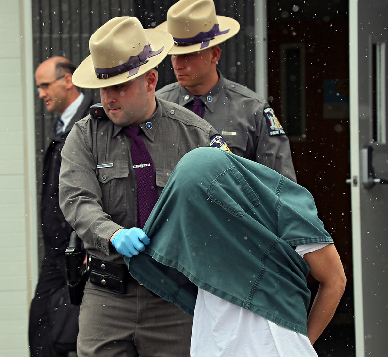 New York State Police lead David Renz out of a state police barracks on Friday.