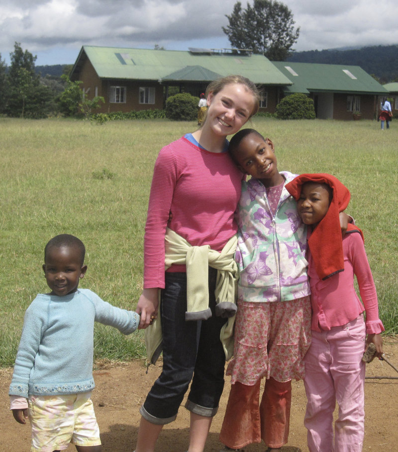 Holly Perkins poses with children at an orphanage in Tanzania during a visit two years ago. She plans to teach ballet there when she returns this month.