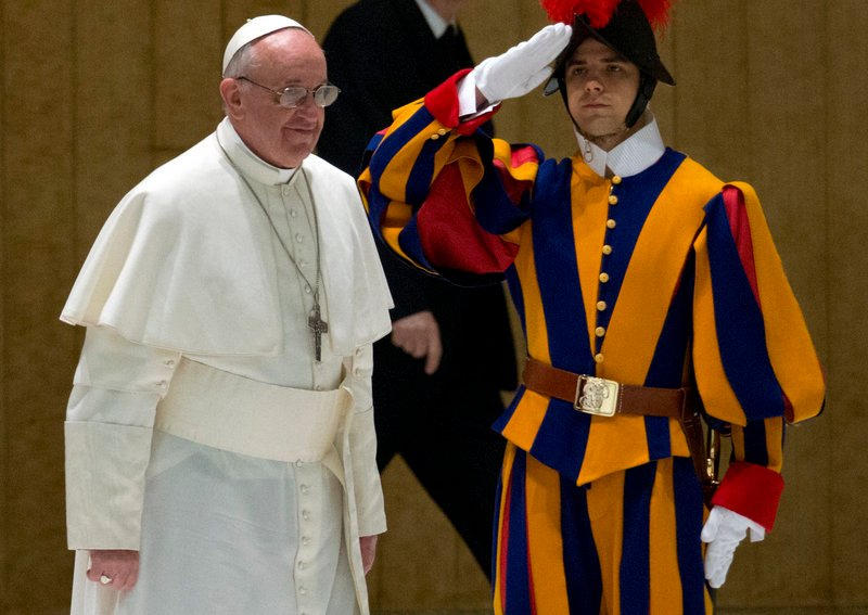 Pope Francis walks past a Swiss guard as he arrives for a meeting with the news media at the Pope VI hall at the Vatican on Saturday.
