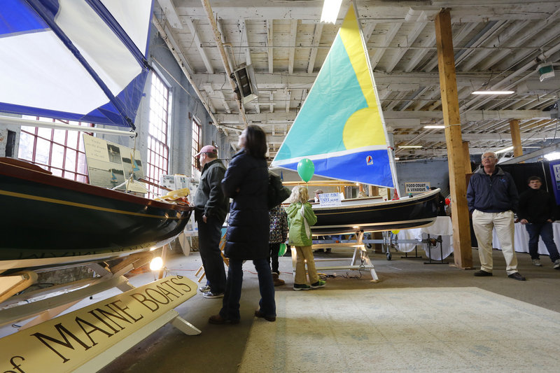 Boat enthusiasts check out custom-built tenders, made by Kennebunkport's Bay of Maine Boats, during the 26th annual Maine Boatbuilders Show in Portland.