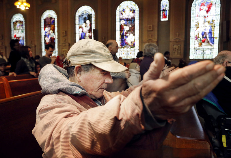 Antonio Hernandez of Portland lifts his hands in prayer Sunday during Mass at Sacred Heart/St. Dominic church in Portland.