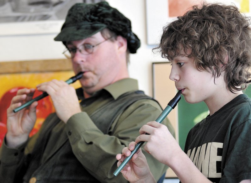 Adam Soosman, left, and Will Fahy, 13, play tin whistles Sunday at the Harlow Gallery in Hallowell. The duo played traditional Irish songs on the instruments during a fundraiser at the gallery on St. Patrick's Day.