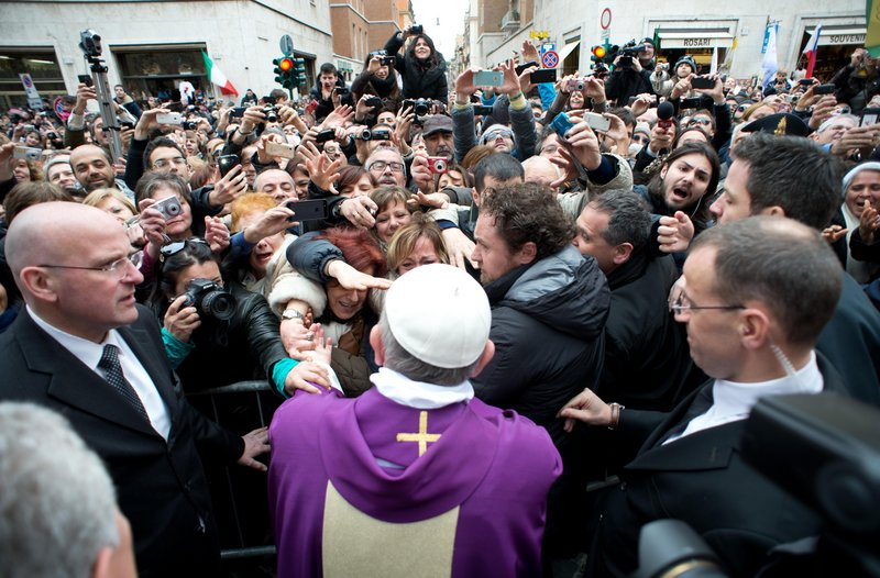 Pope Francis greets onlookers in Rome on Sunday. The pope began his first Sunday as pontiff by making an impromptu appearance to the public from a side gate of the Vatican.