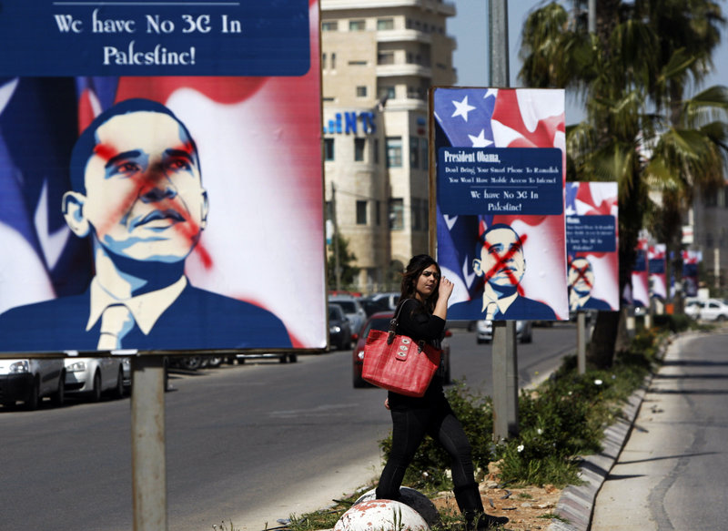 A Palestinian woman in the West Bank city of Ramallah walks past vandalized posters of Barack Obama in the days before the U.S. president's planned visit to the Middle East aimed at restarting Israeli-Palestinian negotiations.