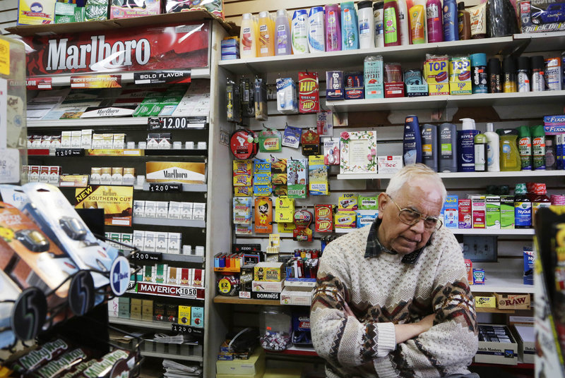 Employee Harry Patel takes a call Monday at Blondie's Deli and Grocery in New York. Under a pioneering citywide proposal, the store's tobacco products would be stored out of sight.