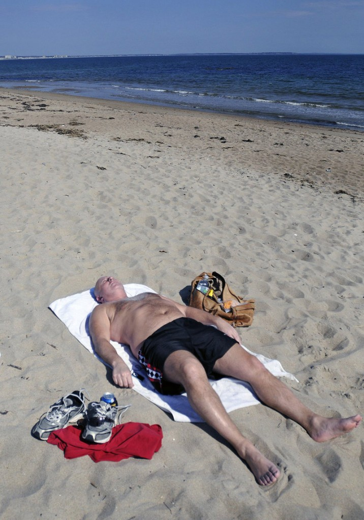 In this March 19, 2012 file photo, Rich Breton of Saco catches some sun rays on an unseasonably warm Monday at Bayview Beach in Saco. What a difference a year makes – Mainers on March 19, 2013 were digging out from the latest snowstorm.