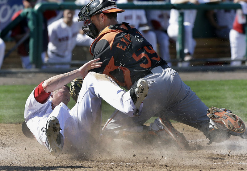 Jeremy Hazelbaker of the Boston Red Sox slides safely into the plate Tuesday, beating a tag applied by catcher Luis Exposito of the Baltimore Orioles. Both are former Sea Dogs players, though not in the same season. Baltimore won the spring-training game, 8-7.