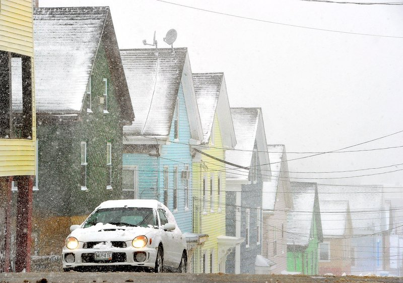 A car climbs the hill and turns onto Cumberland Avenue in Portland as the snow begins to fall on Tuesday, March 19, 2013. In the background, pastel colored houses on Smith Street.
