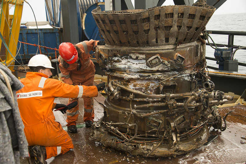 Workers inspect part of an Apollo rocket engine recovered from the bottom of the Atlantic Ocean. Amazon.com CEO Jeff Bezos and NASA announced the recovery Wednesday.