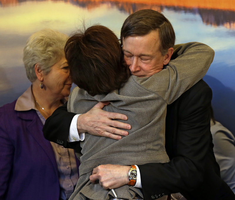 Colorado Gov. John Hickenlooper gets a hug from Rep. Rhonda Fields, D-Aurora, after he signed gun-control bills into law at the Capitol in Denver on Wednesday. Fields co-sponsored bills requiring background checks and limiting the size of ammunition magazines.