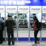 Customers try to use automated teller machines in Seoul. Computer networks at major South Korean banks and television broadcasters crashed simultaneously Wednesday.