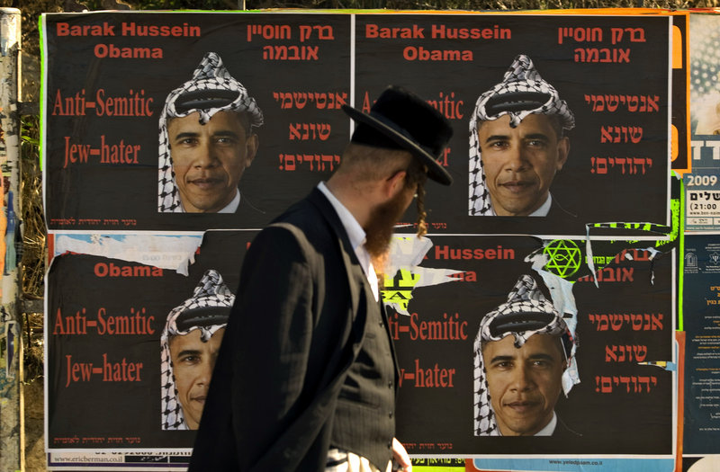 An Ultra Orthodox Jewish man walks past posters depicting President Barack Obama wearing Arab headdress, in Jerusalem, in this 2009 file photo. Obama's assurances of the U.S. commitment to Israel's security remains a tough sell.