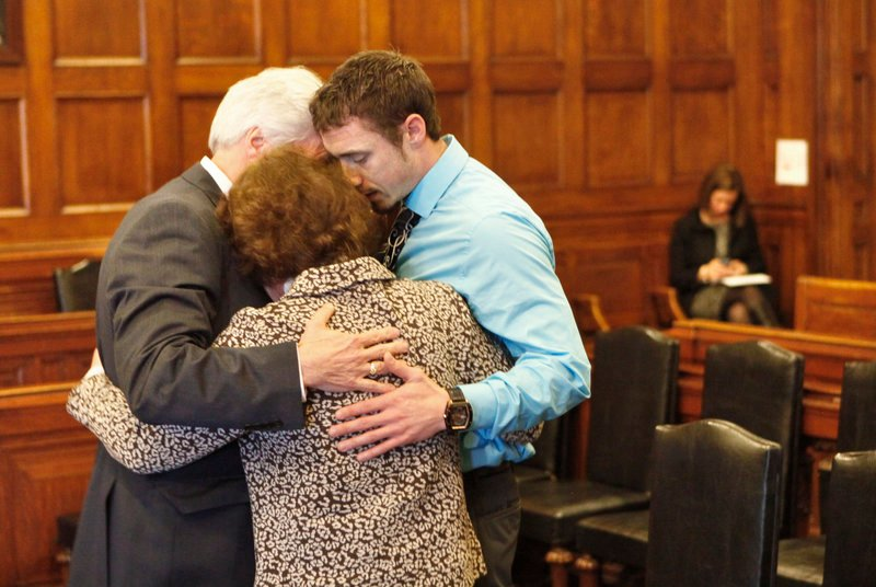 Mark Strong Sr., his wife, Julie, and their son Bradley hug during a recess in Cumberland County Unified Criminal Court in Portland on Thursday. Mark Strong was sentenced to 20 days in jail and ordered to pay $3,000 in fines.