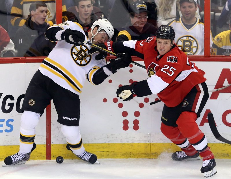 Boston's Aran Johnson and Ottawa's Chris Neil joust along the boards during Thursday night's game in Ottawa, won by the Bruins on a goal in the third period.