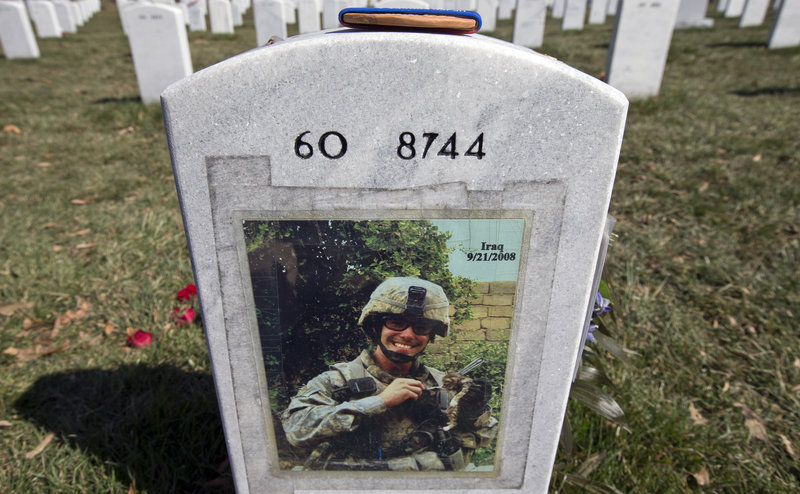 "A photo is attached to the back of the tombstone of Army 1st Lt. Thomas J. Brown, a casualty of the Iraq war, in Arlington National Cemetery. ""The war had three unique phases, each requiring a change in political and military policies,"" says a Marine veteran."