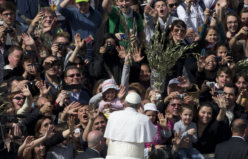 Pope Francis is cheered by a crowd estimated at 250,000 after celebrating his first Palm Sunday Mass as pope in St. Peter's Square at the Vatican on Sunday.