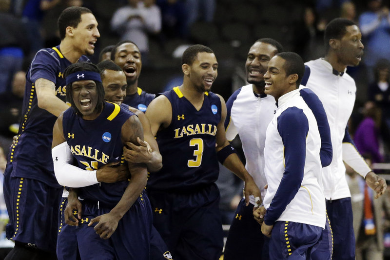 Tyrone Garland, left, celebrates with his teammates after his basket with 2 seconds remaining gave LaSalle a 76-74 win over Mississippi and a spot in the West Regional semifinals against Wichita State.