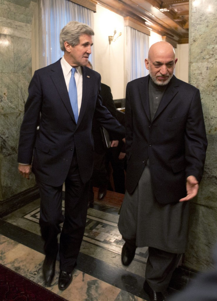 Secretary of State John Kerry walks with Afghan President Hamid Karzai to a meeting at the Presidential Palace in Kabul on Monday.