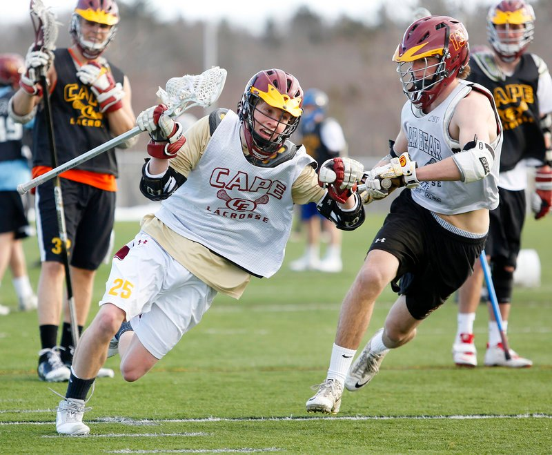 Photos by Derek Davis/Staff Photographer Cape Elizabeth junior Matt Fisher, center, works his way past junior defenseman Trevor Gale during the first lacrosse practice on the school's artificial turf field Monday.