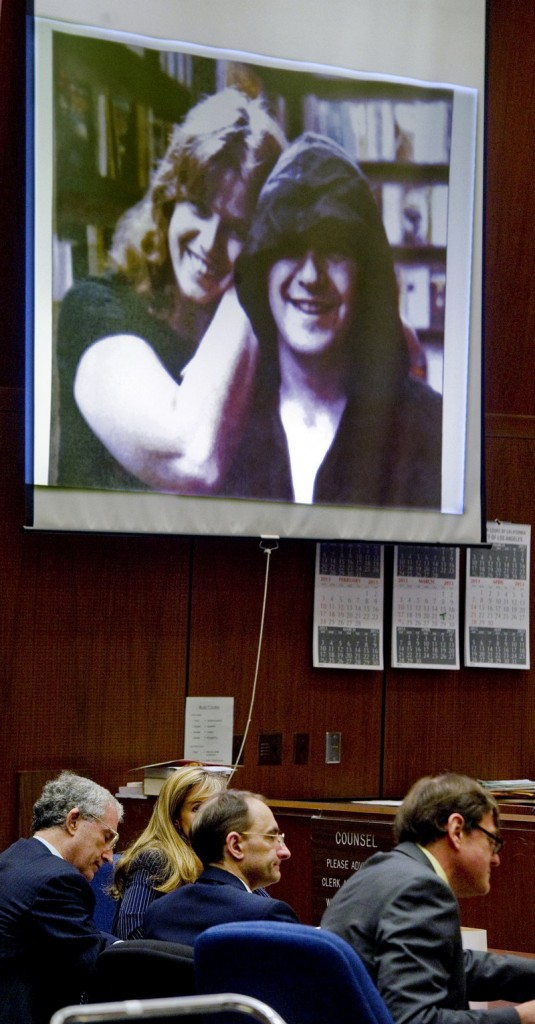 Christian Karl Gerhartsreiter, center, sits with his lawyers in front of a projected photo of Linda and John Sohus in a Los Angeles courtroom Monday.