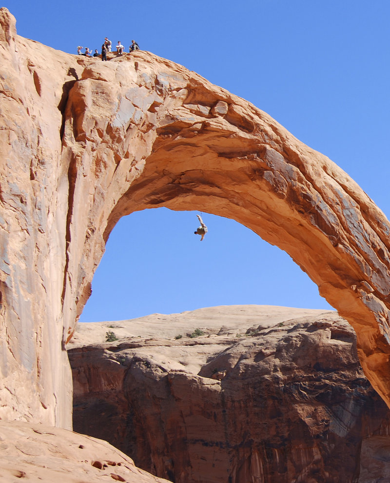 A person swings from the Corona Arch near Moab, Utah, in November. A 22-year-old man was killed Sunday, trying to swing through the opening of the 110-foot-tall, sandstone arch in a stunt made popular on YouTube.