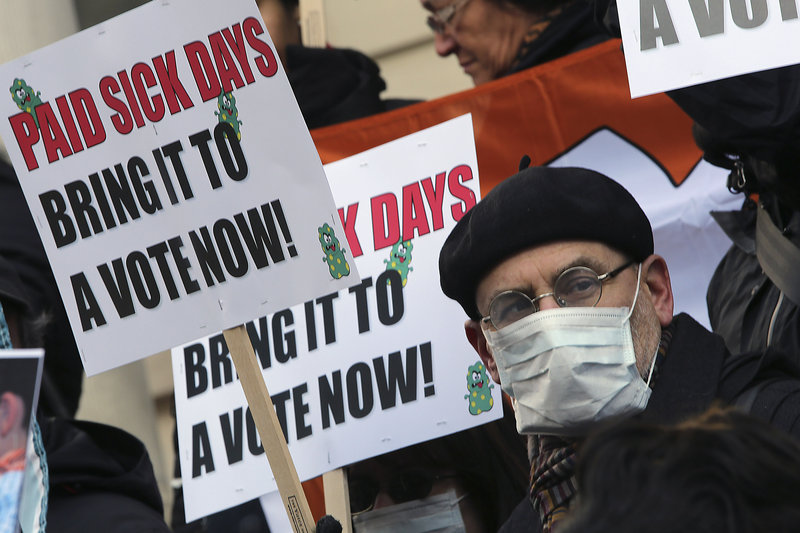 Activists hold signs during a rally at New York's City Hall on Jan. 18 to call for action on a proposal to require employers in New York City to provide paid sick leave. A proposal before Congress would require employers nationwide to allow up to seven paid sick days a year.