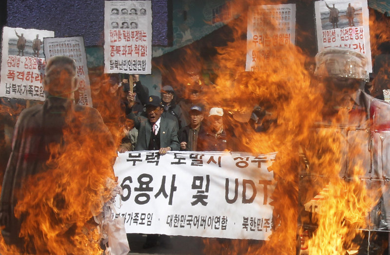 South Korean activists burn cutout pictures of North Korea's founder, the late Kim Il Sung, right, and late leader Kim Jong Il during a rally Tuesday in Seoul, South Korea, to mark the third anniversary of the sinking of the South Korean naval ship Cheonan, which killed 46 sailors.
