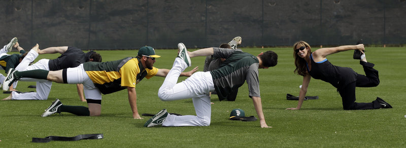 The Athletics, who have learned to stretch their payroll, perform yoga stretches with the help of instructor Katherine Roberts before Wednesday's exhibition game against Colorado in Phoenix.
