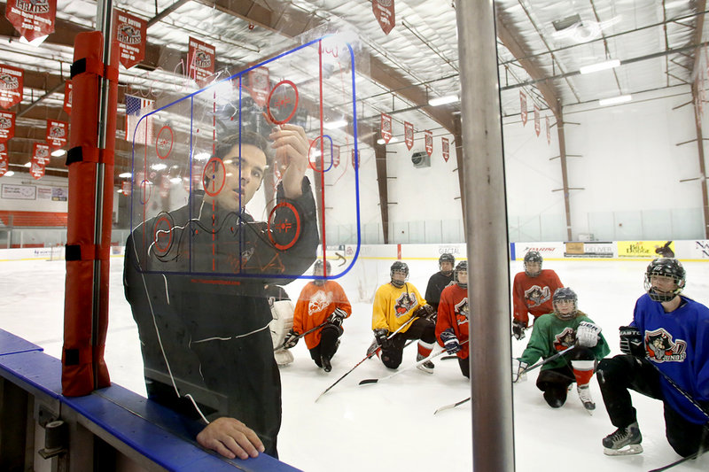 Matt Libby, coach of the Portland Junior Pirates girls' U19 team, diagrams instructions at the MHG Ice Center in Saco on Thursday. And Libby has a lot to offer – he played for both Providence College and professionally for the Portland Pirates.