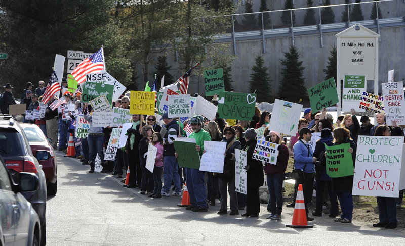 Supporters of both sides of the gun debate gather outside the National Shooting Sports Foundation headquarters in Newtown, Conn., on Thursday.